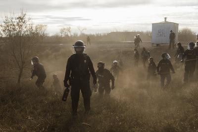 Esta instantánea ganadora del primer premio en Historias en la categoría de Temas Contemporáneos, captada por la fotógrafa canadiense Amber Bracken muestra a un grupo de policías antidisturbios que tratan de dispersar con balas de goma a los manifestantes que protestan en una carretera secundaria junto al oleoducto Dakota Access Pipelines, en Estados Unidos.