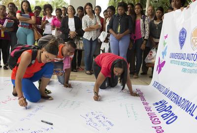 Mujeres escriben sus demandas en un gran cartel durante una manifestación en la Universidad Autónoma de Santo Domingo (UASD), en República Dominicana.
