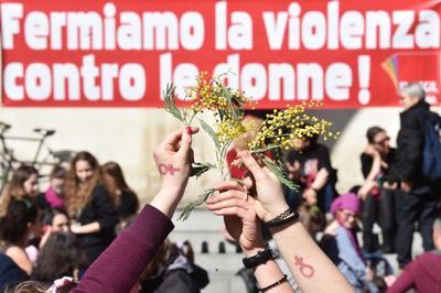 """Mujeres posan con flores bajo una pancarta que reza """"detengamos la violencia contra la mujer"""" en Florencia, Italia."""