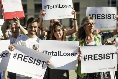 También un grupo de manifestantes de Campact sostienen pancartas en las que se lee '#Resiste' y '#PerdedorTotal'.