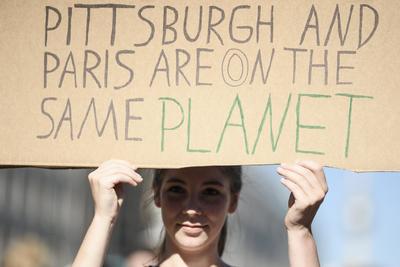 Una manifestante sostiene una pancarta en la que se lee 'Pittburgh y París están en el mismo planeta', durante las protestas.