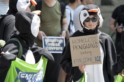 Otros activistas de disfrazados de pingüinos protestan contra la decisión del Gobierno estadounidense de salir del acuerdo.
