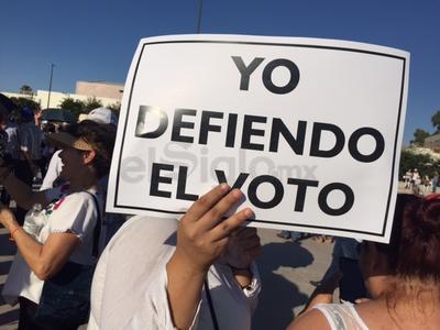 """Durante la marcha la gente portaba pancartas con leyendas de """"Riquelme, Torreón y Coahuila te repudian"""", """"Fuera los Moreira de Coahuila"""", """"Yo defiendo el voto"""", """"Riquelme, Coahuila no te quiere"""", """"Te repudio Riquelme"""", entre otras más, así como algunos recordatorios maternos al PRI, los Moreira y Riquelme."""
