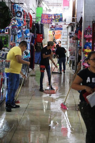 Locatarios del Excuartel Juárez se ayudaron de escobas para sacar el agua de sus negocios.