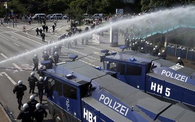 """La situación empezó a empeorar ayer, al detectarse la presencia de un millar de encapuchados en la manifestación de la izquierda radical convocada bajo el lema """"Welcome to hell"""", tras lo que los antidisturbios hicieron uso de cañones de agua a presión para dispersarlos."""