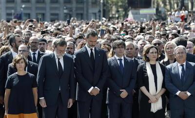 El rey Felipe VI (tercero al centro) encabezó hoy la concentración de un minuto de silencio que autoridades del Estado, Cataluña y Barcelona realizaron en las proximidades a donde un atentado terrorista causó 13 muertos y más de un centenar de heridos.