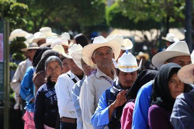 En la imagen resaltan algunos adultos mayores que hacen fila en el banco para extraer los apoyos gubernamentales.