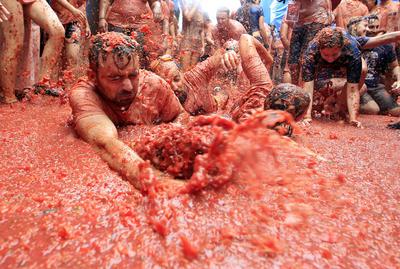 Los asistentes se arrojan toneladas de tomates maduros hasta terminar bañados en pulpa roja.