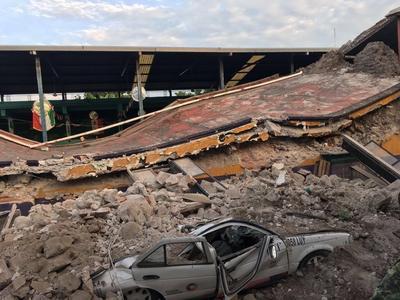Un carro aplastado por escombros de un edificio que se derrumbó a consecuencia del terremoto.