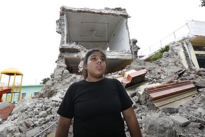 Una niña y detrás su escuela que se derrumbó en el municipio de Jojutla.