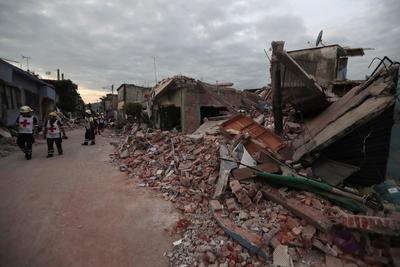 Miembros del Equipo de la Cruz Roja caminan por las calles afectadas por el temblor.
