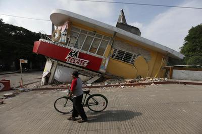 Un hombre con su bicicleta pasa junto a un edificio que se derrumbo hacia atrás en el municipio de Jojutla.