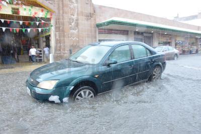 Conductores transitaban con precaución entre el agua para evitar que sus automóviles sufrieran averías.