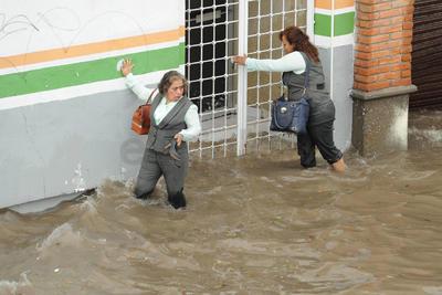Ni Simas se salva. Empleadas del Simas tuvieron que mojar sus pies y ropa ante la cantidad de agua afuera de sus oficinas.