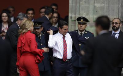 El presidente Enrique Peña Nieto, poniéndose su saco para recibir al Primer Ministro de Canadá en el Palacio Nacional.