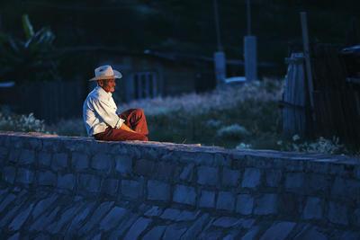 Un adulto mayor descansa sobre el canal que permite la salida de agua de la presa del Hielo.