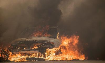 James y Josie Ralstin usaban mascarillas mientras sacaban algunas pertenencias de su hogar mientras una residencia cercana se quemaba.
