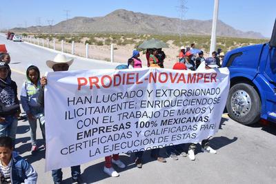 Ejidatarios muestran una manta como protesta en la que se señala a las empresas 'PRODIEL' y 'NOVAMPER'.