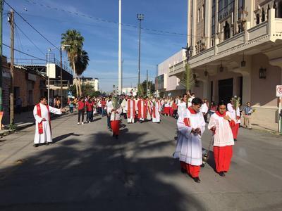 Al término, el obispo encabezó la procesión en la que se ofrecían alabanzas mientras los fieles alzaban sus ramos.