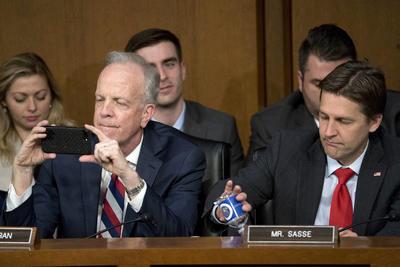 El senador Jerry Moran toma una fotografía con su celular mientras el Zuckerberg está testificando.
