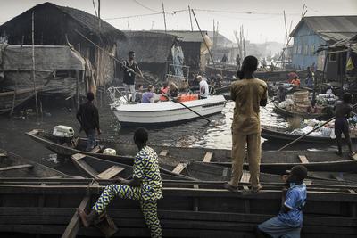 Por Jesco Denzel, muestra a un bote con turistas en Lagos Marina, mientras navegan por la comunidad de Makoko.