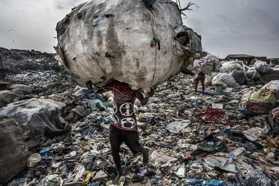 """Fotógrafo: Kadir van Lohuizen, ganador del 1er premio de la categoría """"Environment - Stories"""". Muestra a un hombre mientras carga un enorme lomo de botellas recogidas para su reciclaje en el vertedero de Olusosun en Lagos, Nigeria"""