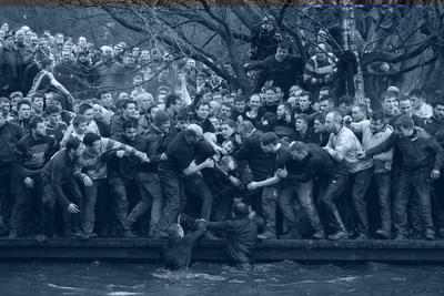 """La imagen captada por el fotógrafo Oliver Scarff, ganador del primer premio de la categoría """"Sports - Singles""""; muestra a los miembros de equipos contrarios, los Up'ards y Down'ards, luchando por el balón durante el histórico y anual partido de fútbol Royal Shrovetide."""