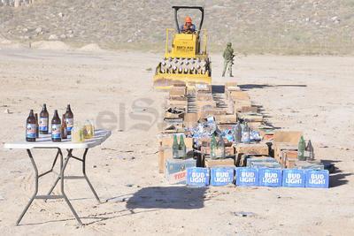 Botes y botellas con contenido alcohólico vendido ilegalmente fueron apisonados por la aplanadora.
