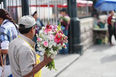 Al exterior comerciantes ofrecen flores frescas para llevar hasta la imagen de San Jorge.