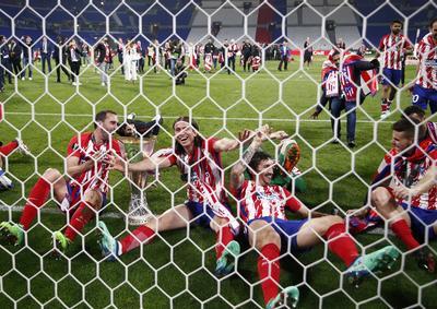 Jugadores del Atlético celebran después del juego con el trofeo en sus manos.