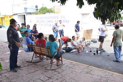 """Con botellas de refresco de cola y piezas de pan, sacaron a los pequeños de las casas para que los acompañaran en la protesta, ya que dijo una de las vecinas que """"no hay agua por la falta de luz para bañarlos y no fueron a la escuela""""."""