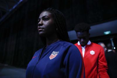 La seleccionada estadounidense Brianna Pinto junto a Alphonso Davis de Canadá durante la ceremonia de elección de sede en Moscú.