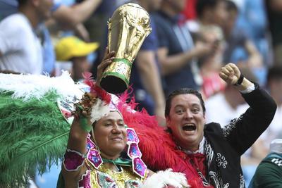 Aficionados mexicanos, uno sosteniendo una imitación de la Copa del Mundo.