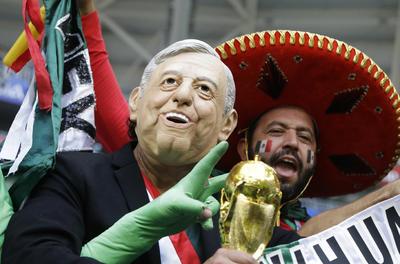 Los fanáticos mexicanos, uno con la máscara del recién electo presidente de México, Andrés López Obrador, aplauden antes de la ronda de 16 partidos entre Brasil y México en la Copa Mundial de fútbol 2018 en el Samara Arena.