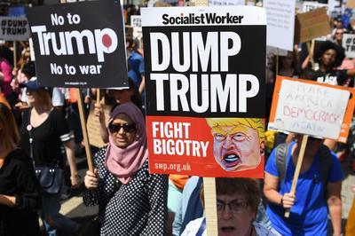 Los manifestantes sostienen pancartas que se reúnen después de una marcha opuesta a la visita del presidente estadounidense Donald Trump.