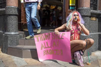 Una drag queen posa con una pancarta durante una protesta en contra del presidente de los Estados Unidos.