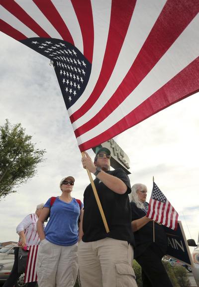 Fue flanqueado por ciudadanos con banderas estadounidenses y carteles de la campaña electoral de 2008, en la que el homenajeado aspiró a la Presidencia pero perdió ante Barack Obama.