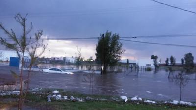 Un vehículo  atraviesa una calle inundada.