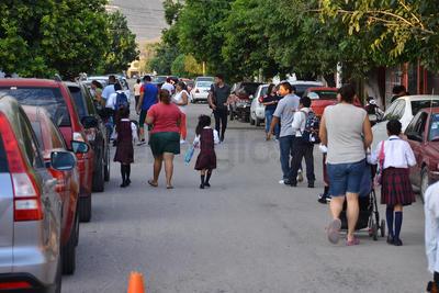 Padres de familia llevando a sus hijos al inicio del ciclo escolar.