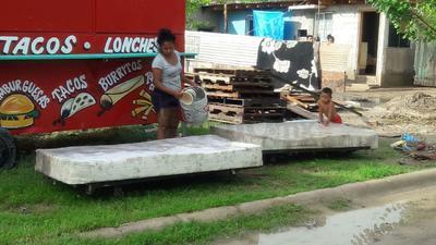 Una ciudadana lava el colchón luego de la inundación que se registró en Piedras Negras.