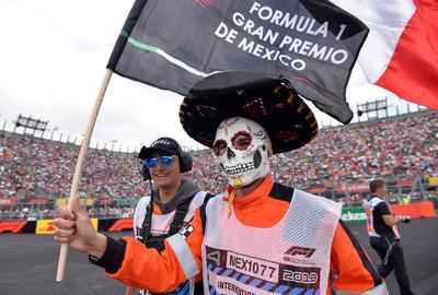 Un asistente maquillado como Catrina agita una bandera durante el Gran Premio de México.,