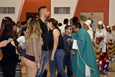 Los presentes van a tomar la hostia ante el sacerdote.