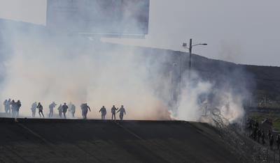 Un grupo de migrantes de la caravana de centroamericanos que avanzó hoy hacia la garita de San Ysidro (EE.UU.) se desvió de la ruta prevista para intentar cruzar el muro fronterizo por otros puntos, en tanto la policía fronteriza estadounidense les lanzó gas lacrimógeno.