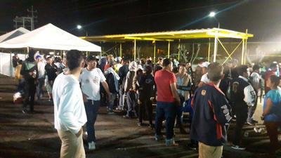 Migrantes aguardan para ser enviados al albergue temporal.
