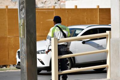En la sombra. Oficial observando la afluencia vehicular en la parte trasera de la Plaza Mayor. Calle Ramón Corona y Allende.