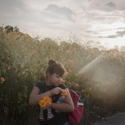 Niña recogiendo flores durante el día de una caminata de 50 kilómetros de la caravana migrante entre Tapanatepec y Niltepec, por Pieter Ten Hoopen