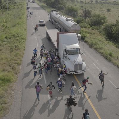 Fotografía tomada por Pieter Ten Hoopen el 30 de octubre de 2018 y cedida por la organización World Press Photo (WPP), que muestra a personas corriendo hacia un camión que paró para llevarlos, afuera de Tapanatepec.