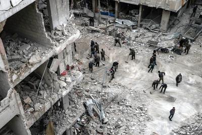 Fotografía publicada como parte de la historia 'Syria, No Exit' que muestra a personas que inspeccionan el 22 de febrero de 2018 los escombros de los edificios dañados después de varios ataques aéreos el día anterior, en Douma, la localidad de Guta (Siria).