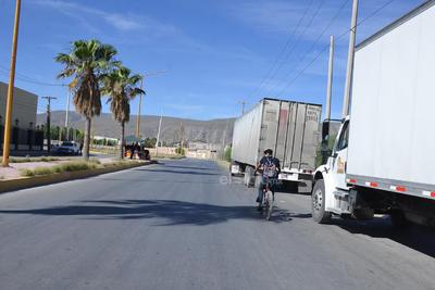 Las personas que se animan a circular con su bicicleta tienen que lidiar con los diferentes tipos de vehículos estacionados por el bulevar Ferropuertos y exponerse a los carros que circulan a altas velocidades.