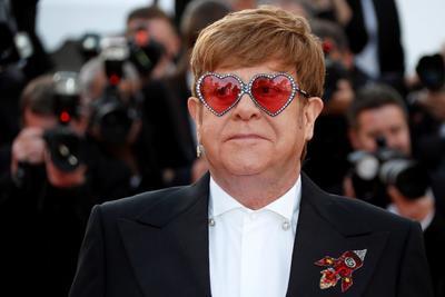 El autor de canciones como Your song -que ha estado sonando en cada alfombra del festival desde su inauguración el martes- completaba su atuendo con unas llamativas gafas en forma de corazón y con los cristales rojos.
